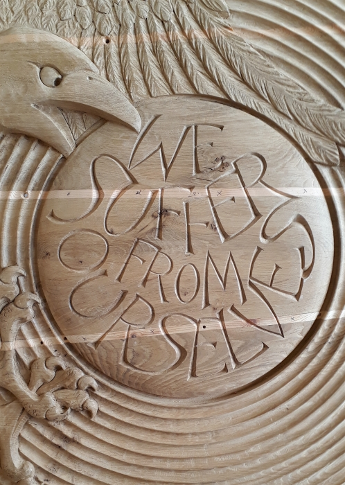 'We Suffer' - detail from larger relief carving